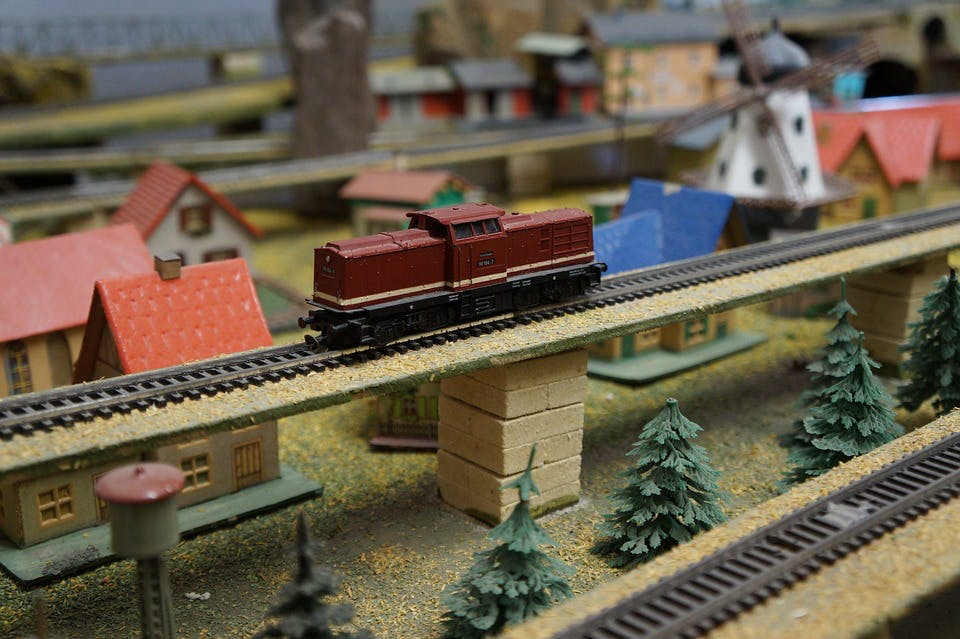 Modellbahn-Landschaft mit Häusern, Gleisen und einer Lokomotive