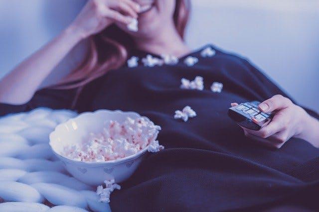 Frau isst Popcorn beim Fernsehen.