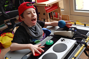 Seated young boy using adapted gaming controls