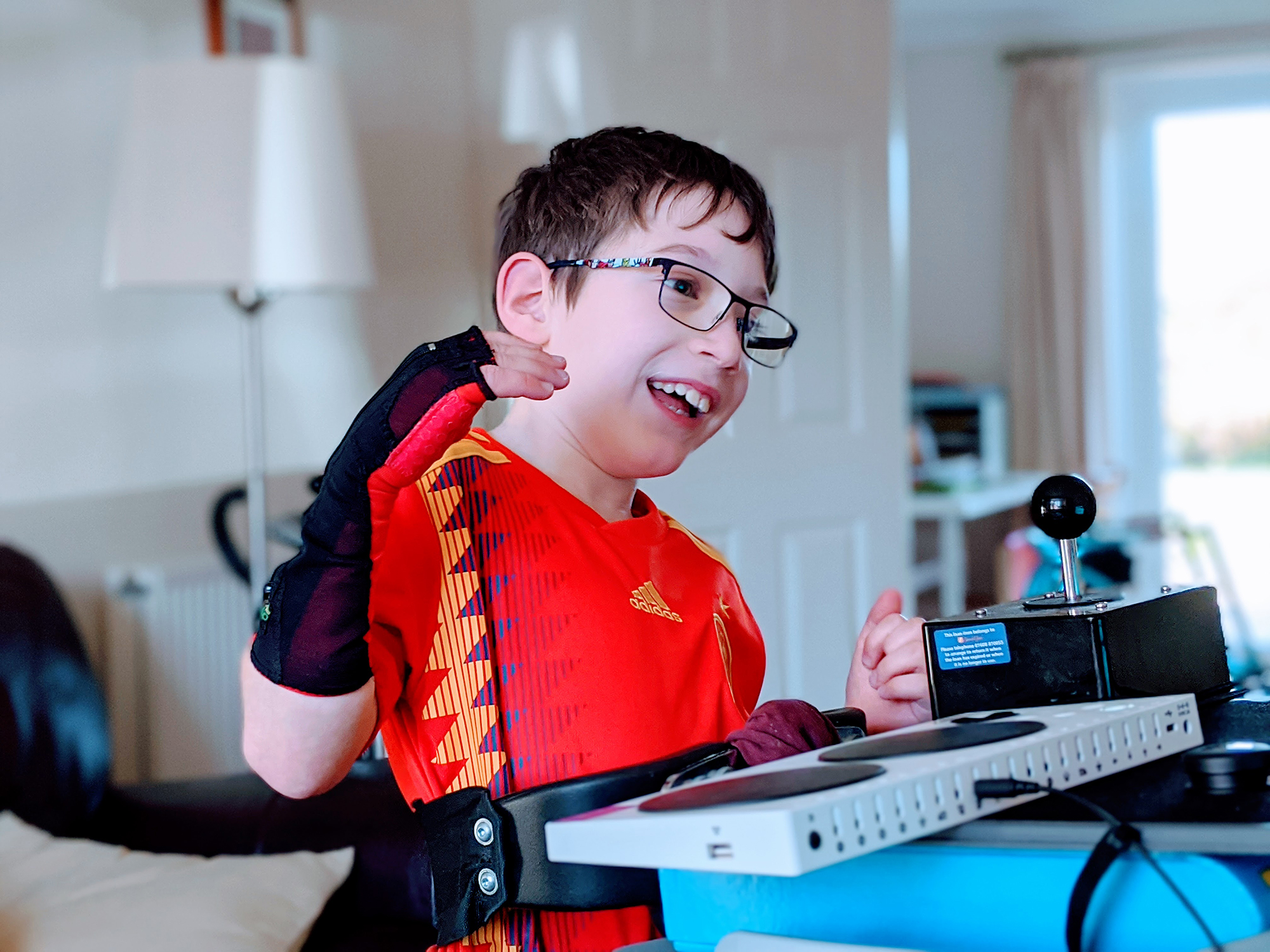 a young boy wearing a wrist brace and a red football tshirt plays with an xbox adaptive controller and a large joystick