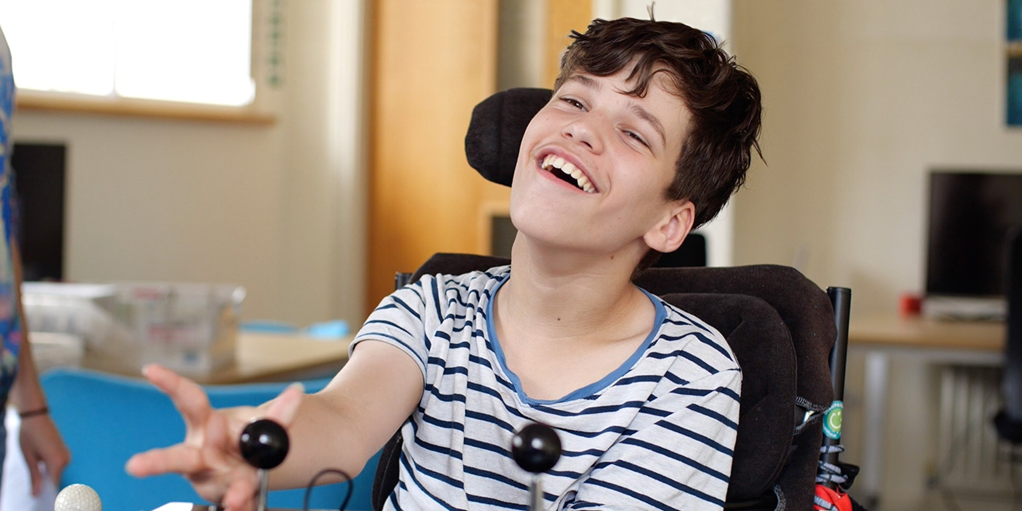 a young boy wearing a blue and white striped tshirt plays with two large joysticks