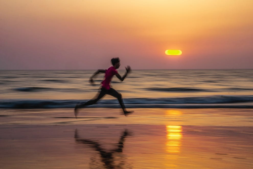 boy sprinting on beach sunset
