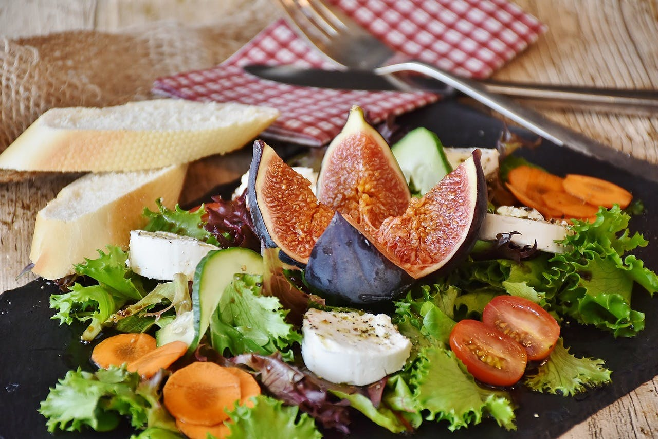Close-up of vegetable salad and slices of bread on a board