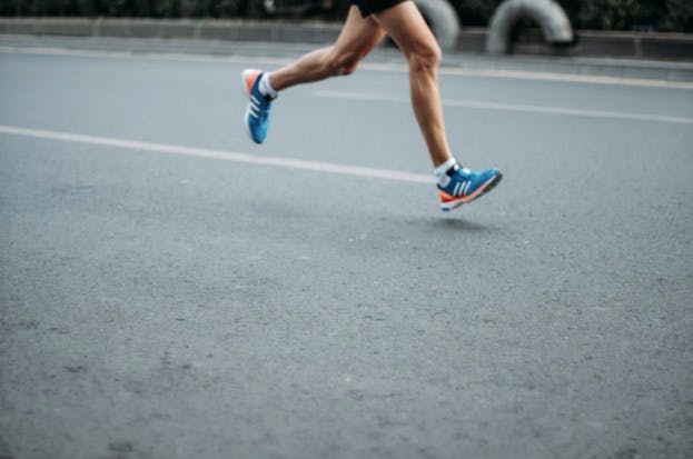 A man running on the street with proper running form and shoes