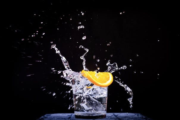A glass of sparkling water and a slice of lemon on a black background