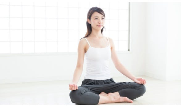 Woman relaxing in the easy pose to address her knee pain