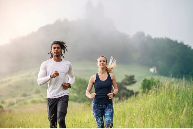 Man and woman running together, with a misty forest behind them