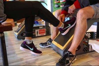 Close-up of man and woman's legs, wearing training shoes, at the gym