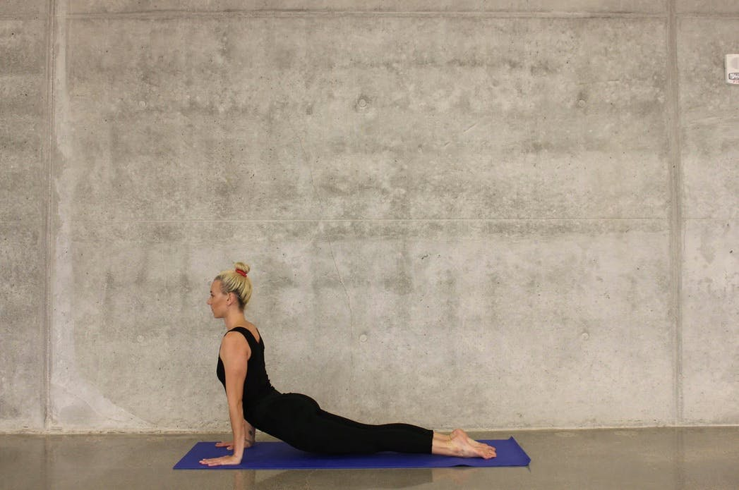 Blonde woman doing yoga on the floor, in front of a concrete wall