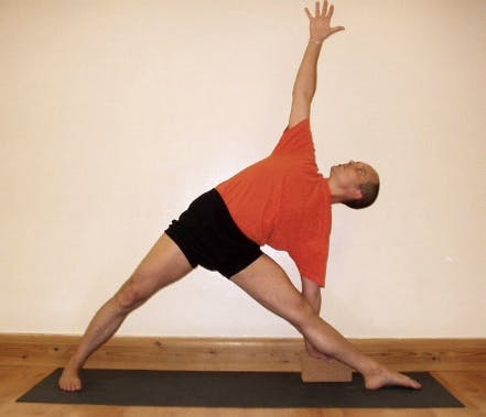 Man doing a yoga move called the Triangle Pose in order to help his knees