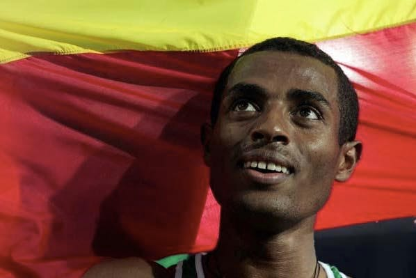 Close-up of Kenenisa Bekele in front of the Ethiopian flag