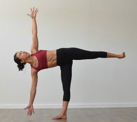 Woman doing the supported half moon pose for knee pain