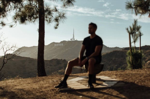 Man sitting on the top of the hill. Hollywood sign can be seen behind.