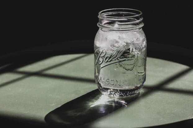 A jar full of water on a table and its reflection