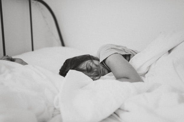 Woman sleeping o a bed with white sheets