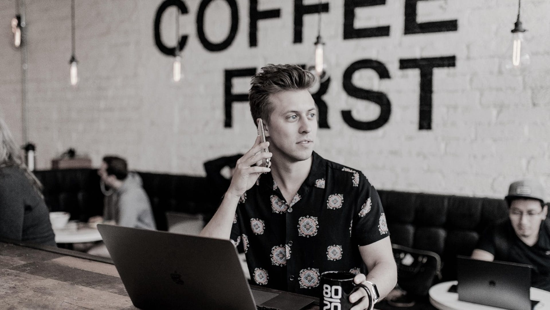 Coffee shop owner working on a laptop and talking on the phone