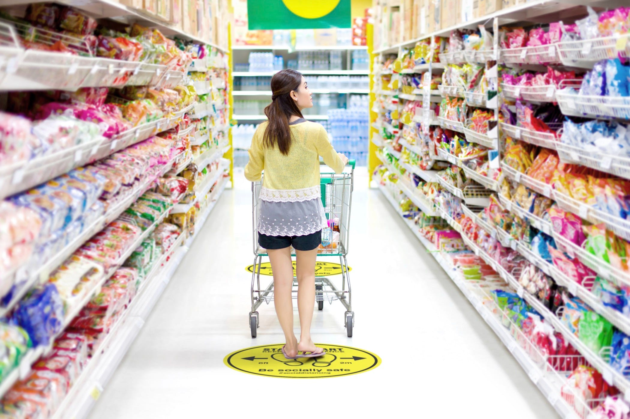 Floor sticker showing safety practices while woman shops in a grocery store