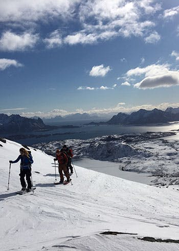 Splitboard snowboarders hiking Lofoten Fjords