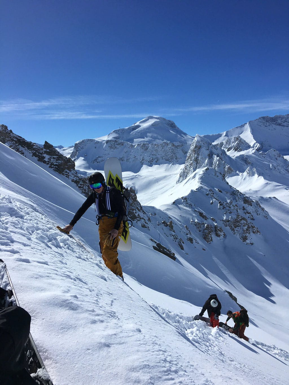 Backcountry freeride snowboarders hiking