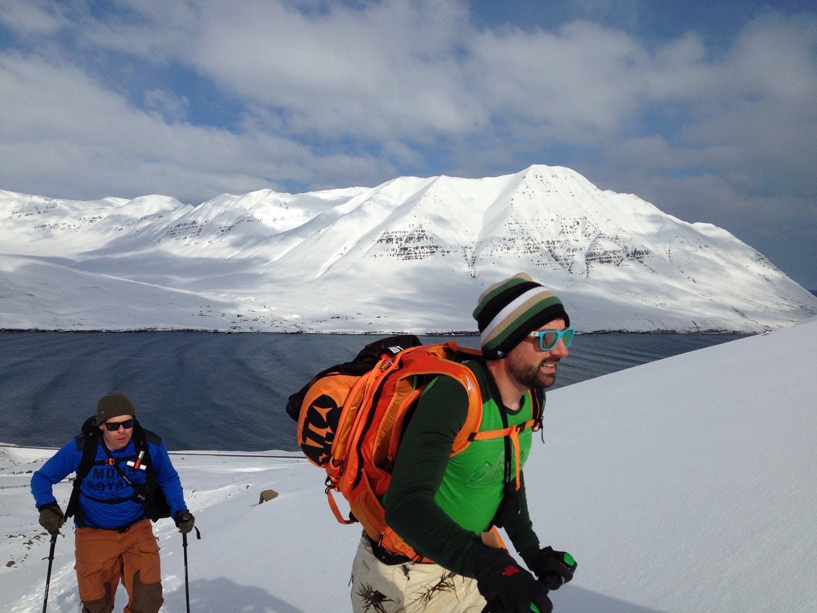Splitboarders hiking next to sea Iceland