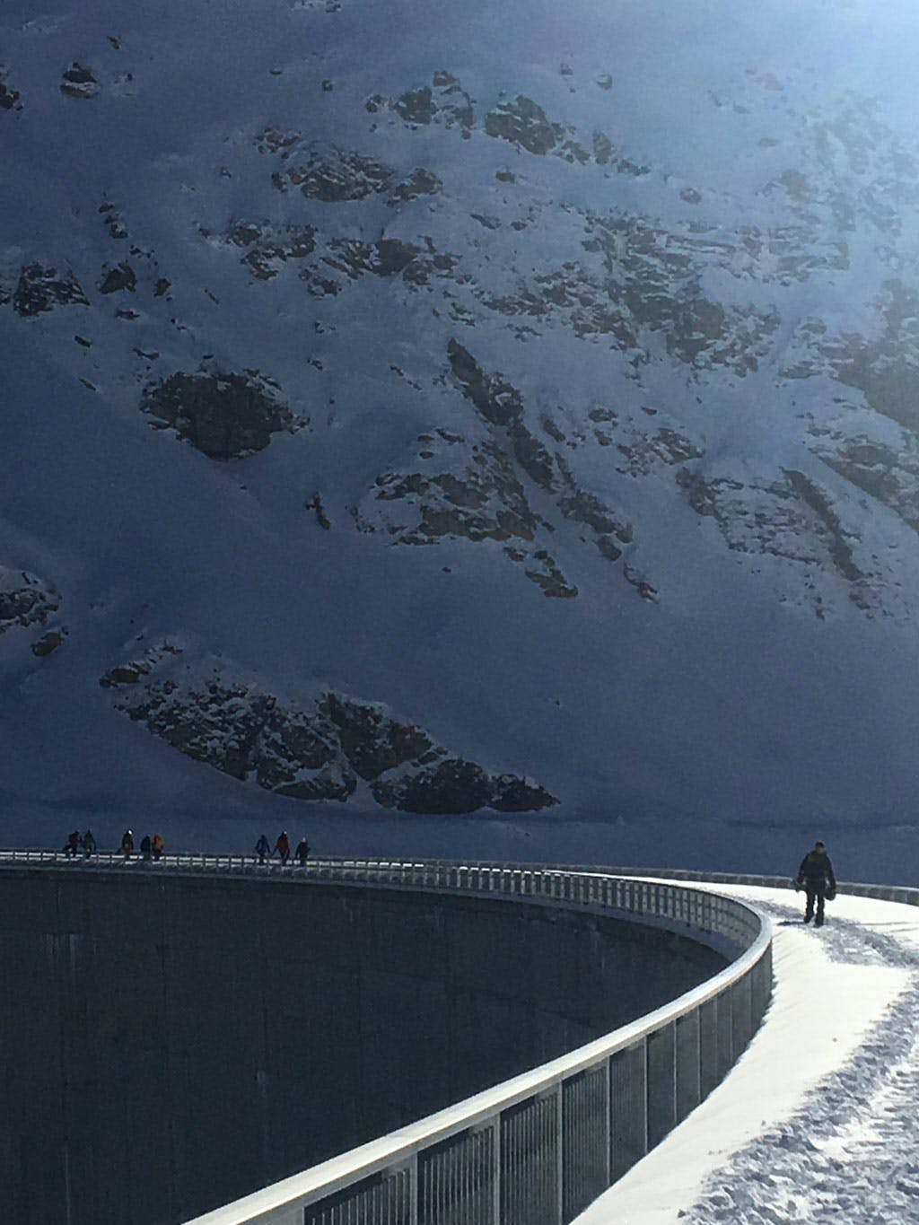 snowboarders hiking next to dam