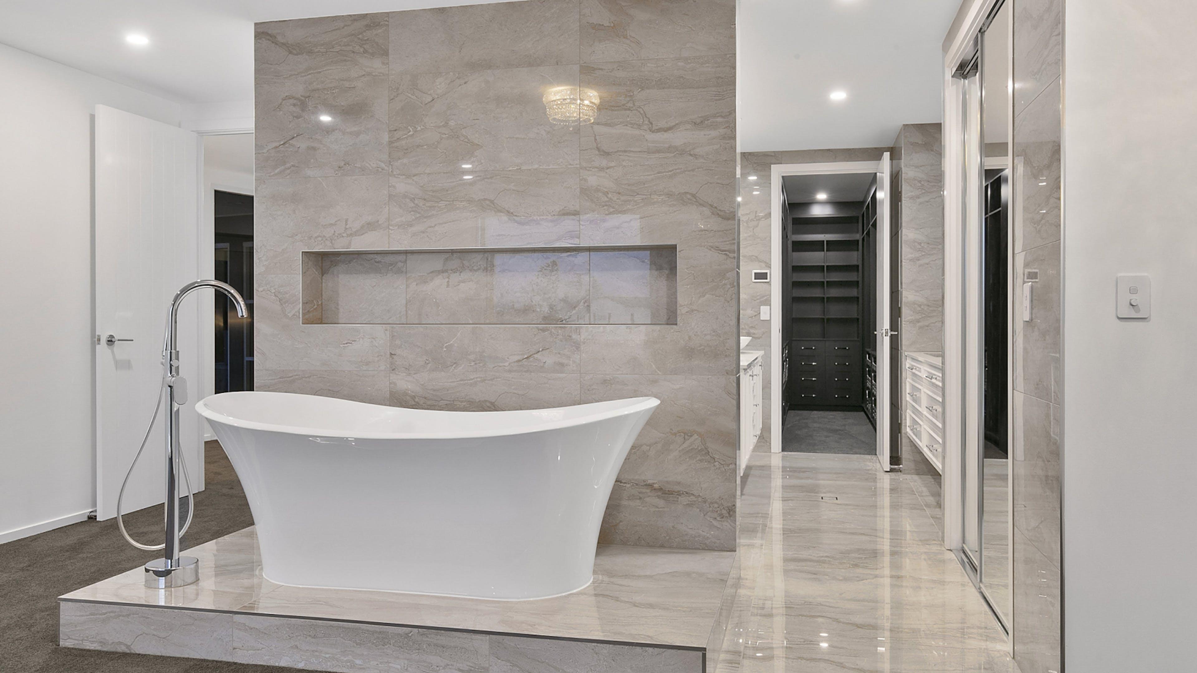 A modern, luxurious bathroom remodelling including high end bathtub done by Streamline Cabinets.