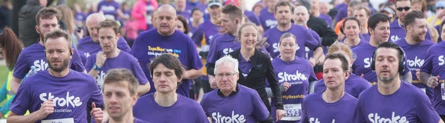 Image showing a huge group of runners all in purple t-shirts, running in a marathon type race.