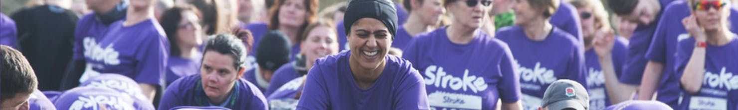 Banner image showing a laughing woman with a sea of other people in the background, all wearing purple t-shirts.