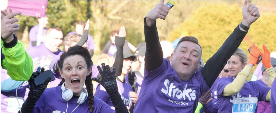 An excited man and woman cheering and throwing their hands in the air to celebrate completing a run, both dressed in purple t-shirts.