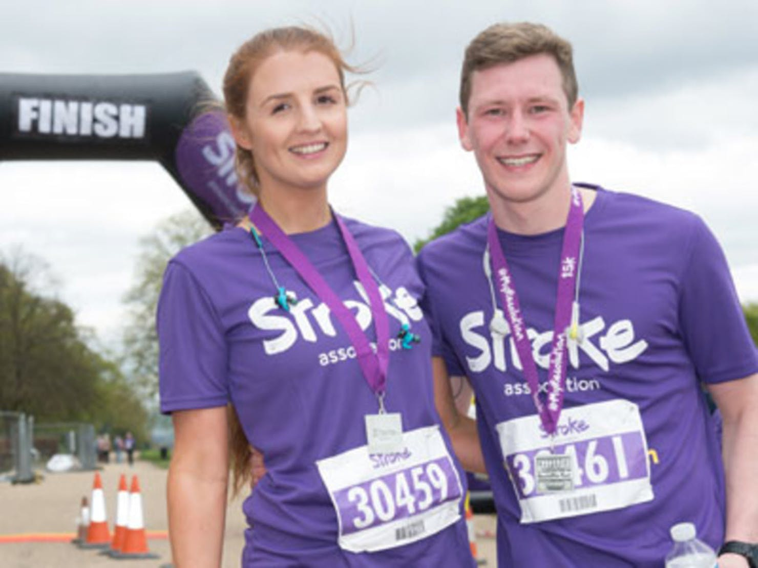 A man and a woman standing at the finish line of a race, both wearing purple t-shirts and medals.