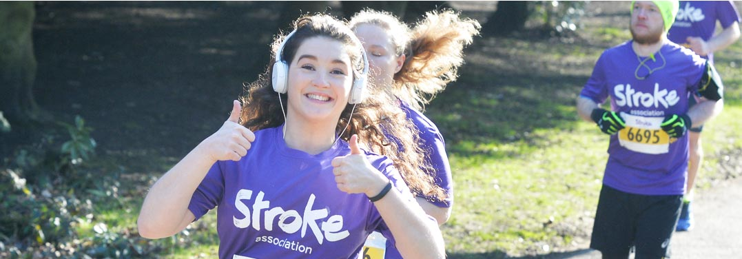 A woman doing a thumbs up, wearing white headphones and wearing a purple t-shirt. She's running and there are a few other women in the background also running.