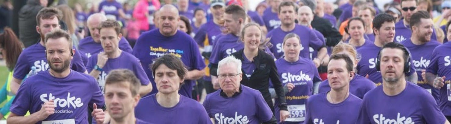 Banner image showing a sea of people all in purple t-shirts running in a marathon.