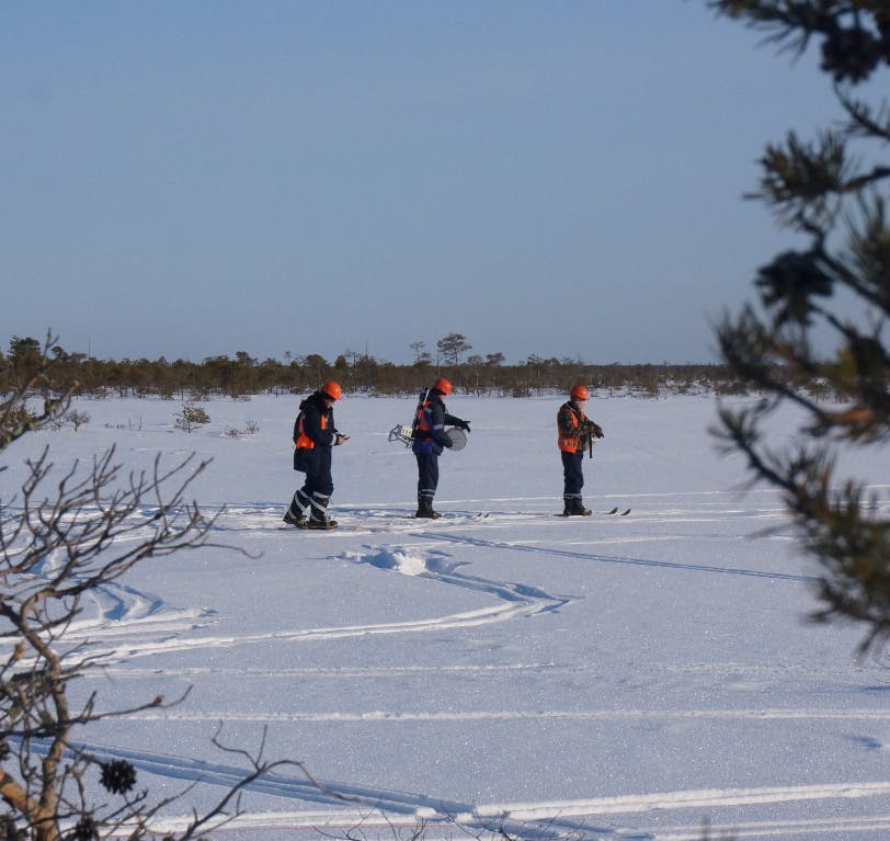 Three people deploying STRYDE nodes for a seismic survey in the snow
