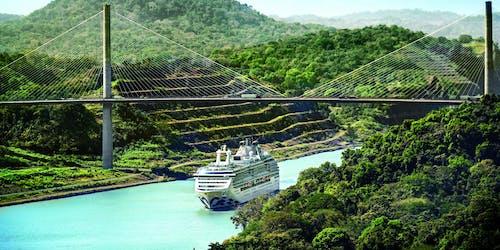 Island Princess kryssar mellan en smal kanal med gröna berg runtomkring.