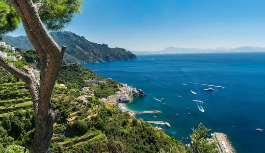 Bild tagen från höga berg ut på Amalfikusten med båtar i vattnet.
