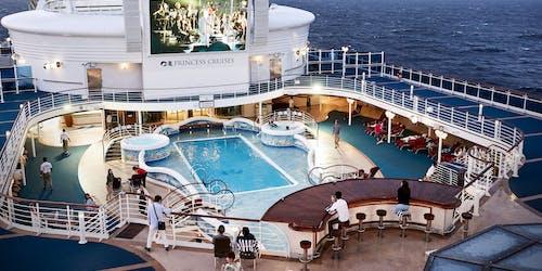 Bild uppifrån på fartyget Diamond Princess poolområde, i överkant syns också fartygets stora bio-skärm.