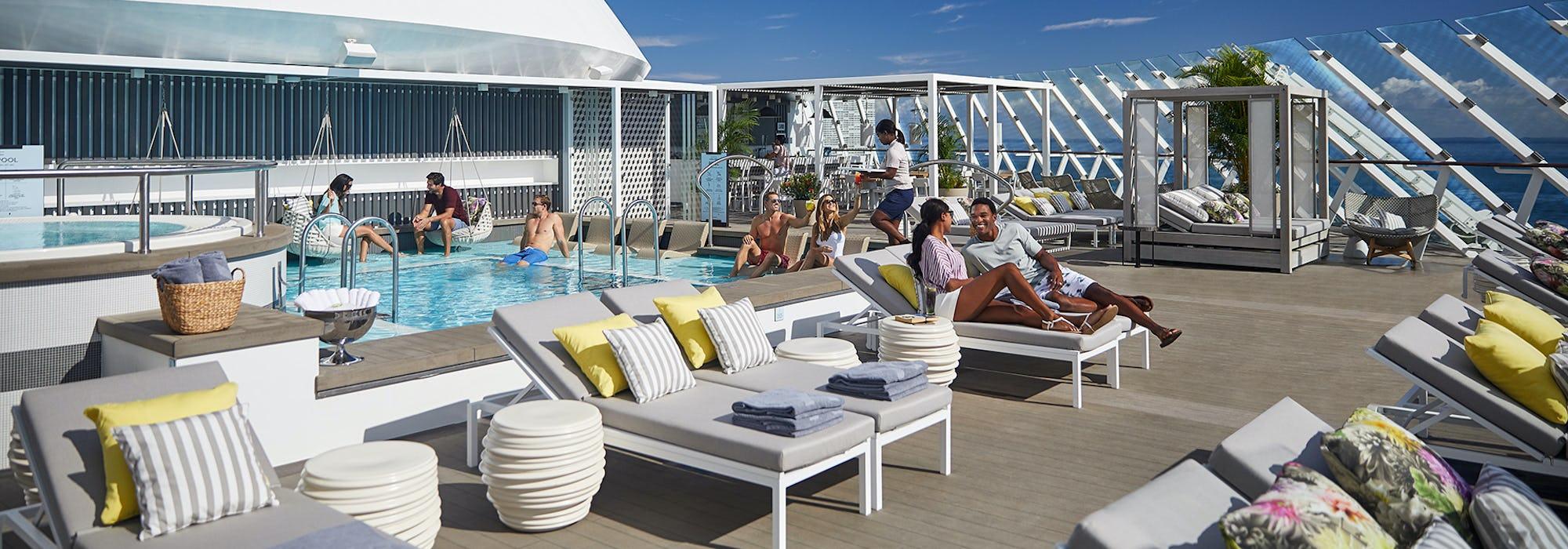 Soldäcket på Celebrity Apex med fler människor i solstolar och en pool till vänster.