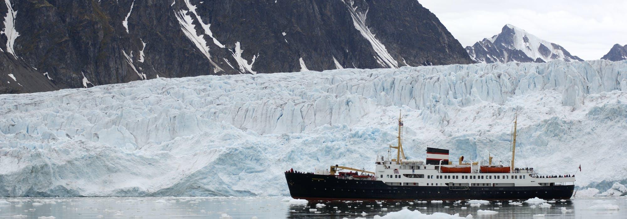 Fartyget MS Nordstjernen kryssar sig fram i islandskapet på Svalbard med isberg och snötäckta berg i bakgrunden.