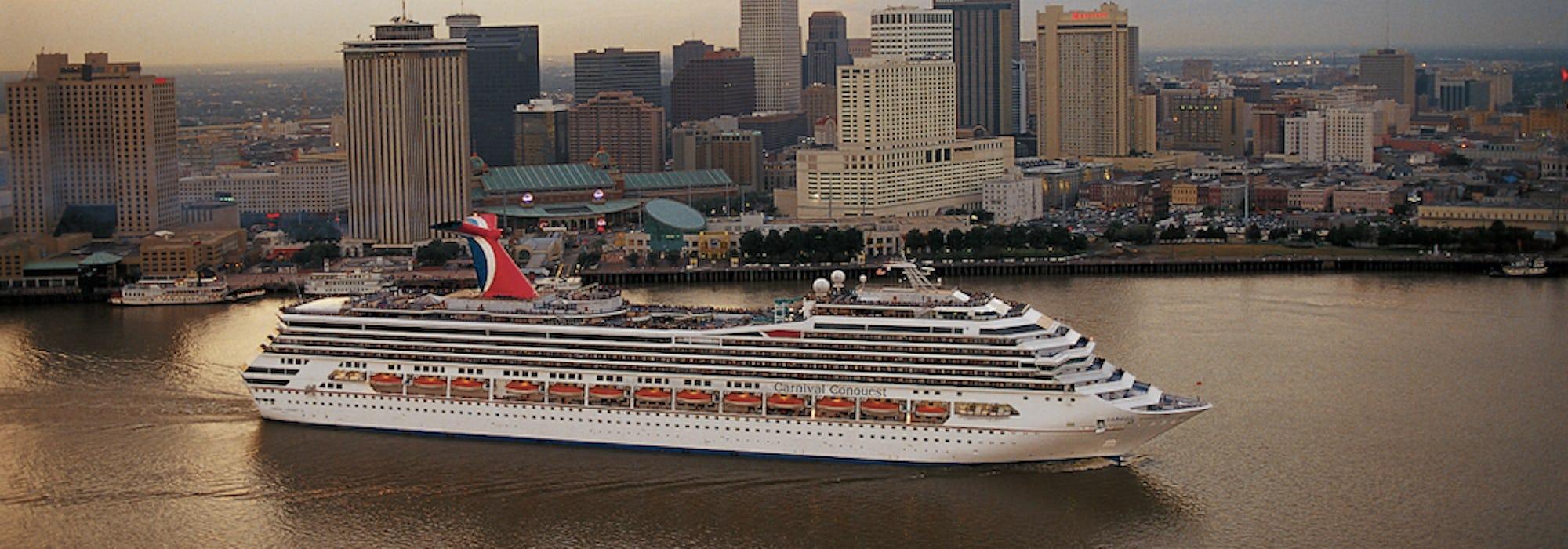 Fartyget Carnival Conquest kryssar fram framför flera skyskrapor.