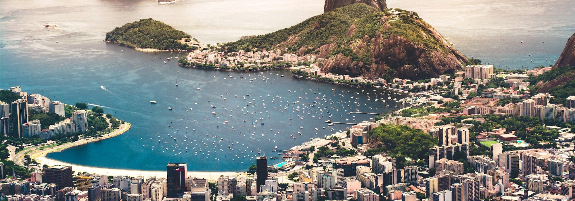 Foto på Rio de Janeiro från ovan med byggnader, berg och kristallblått vatten.