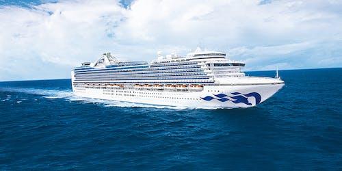 Bild tagen från sidan medan fartyget Emerald Princess kryssar fram i blått vatten.
