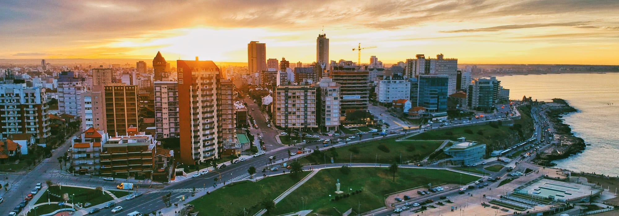 Bild på Buenos Aires kustlinje i solnedgången med byggnader till vänster och havet till höger.