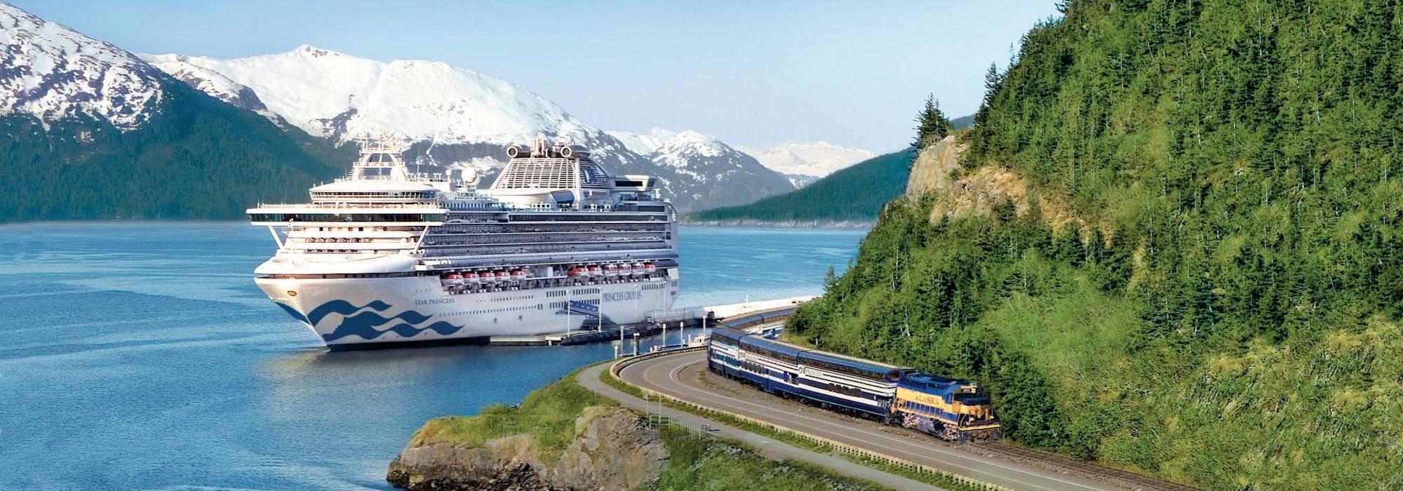 Fartyget Star Princess kryssar fram mellan snötäckta berg och skog. Till höger i bild syns även ett tåg.