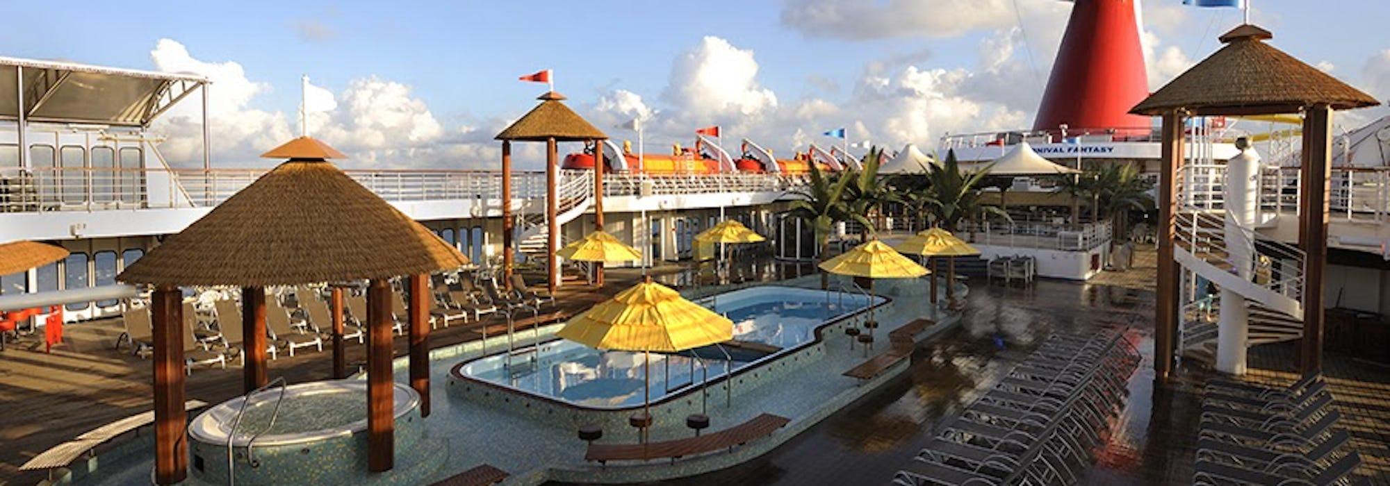 Bild på Carnival Fantasy's sol- och pooldäck med flera solsängar, jacuzzi och en pool.