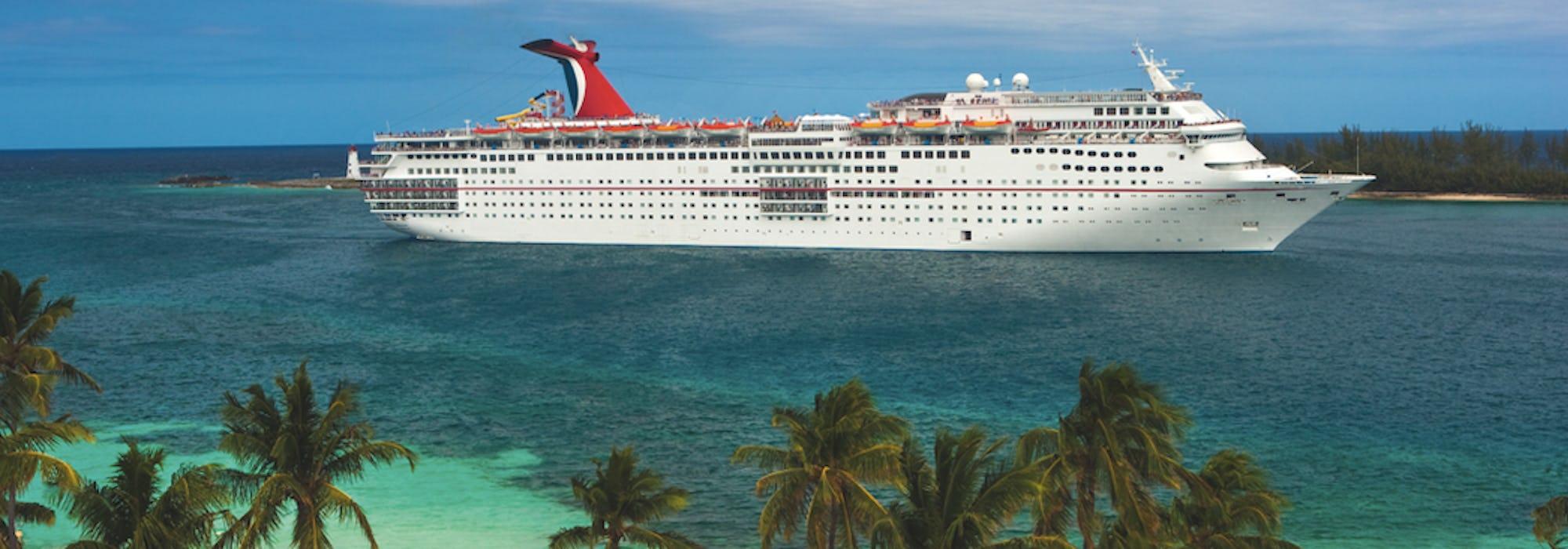 Carnival Sensationen ligger i vattnet utanför en karibisk ö med snövit strand och palmer.
