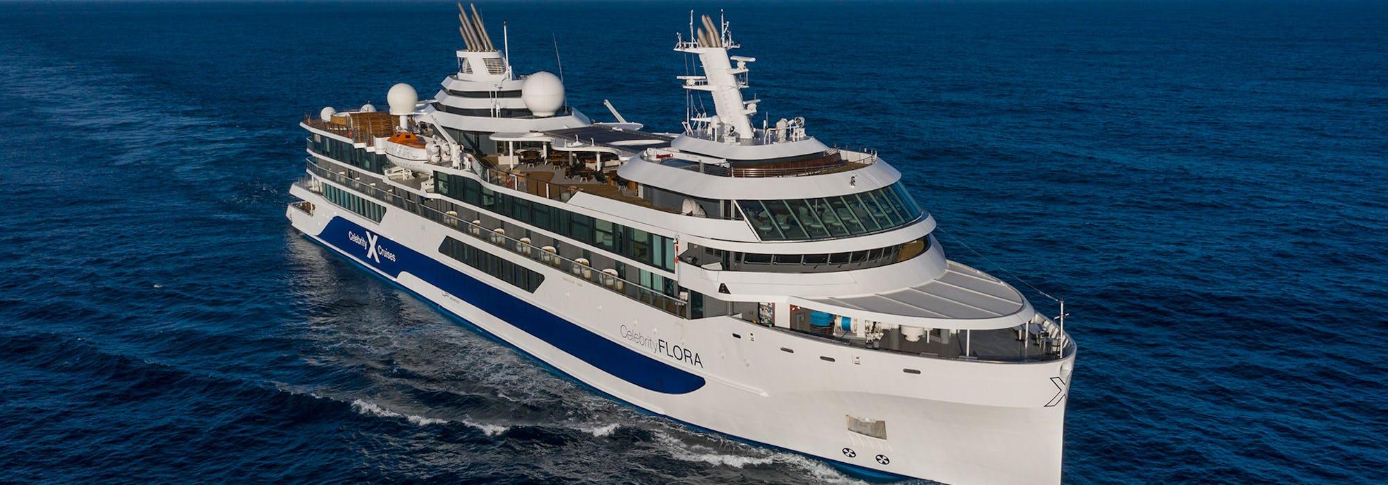 Det mindre fartyget Celebrity Flora kryssar sig fram i klartblått vatten.