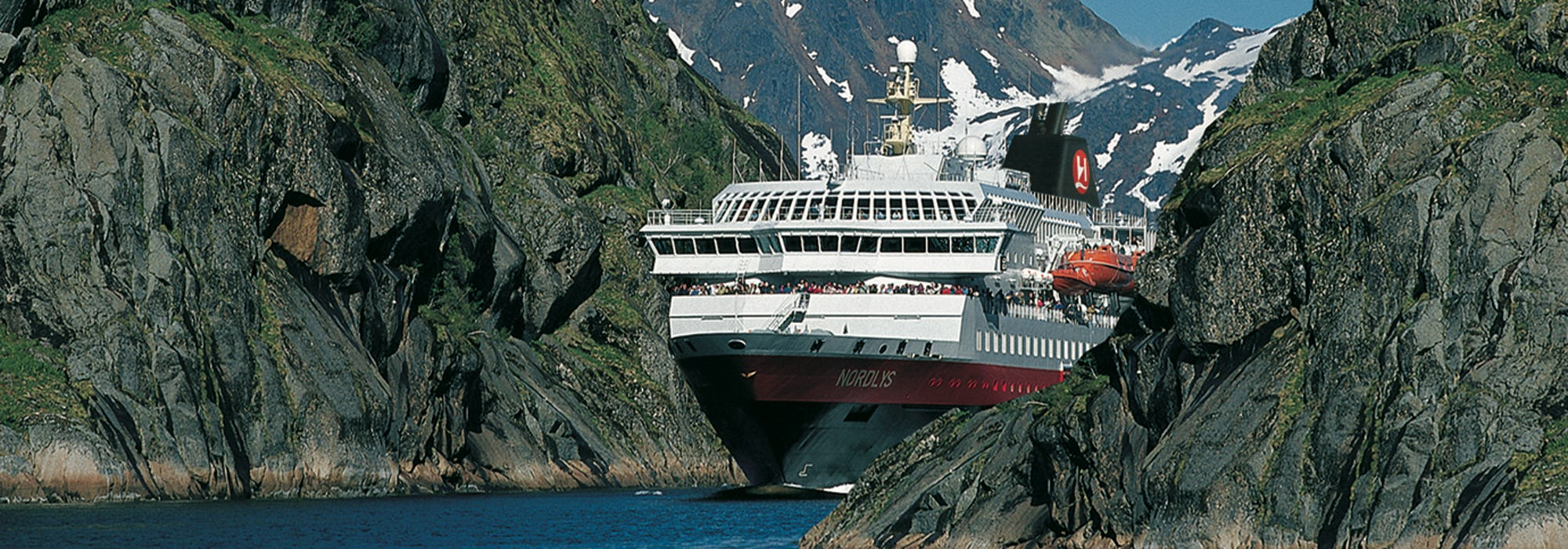 Fören på MS Nordlys sticker fram mellan bergen i de norska fjordarna.