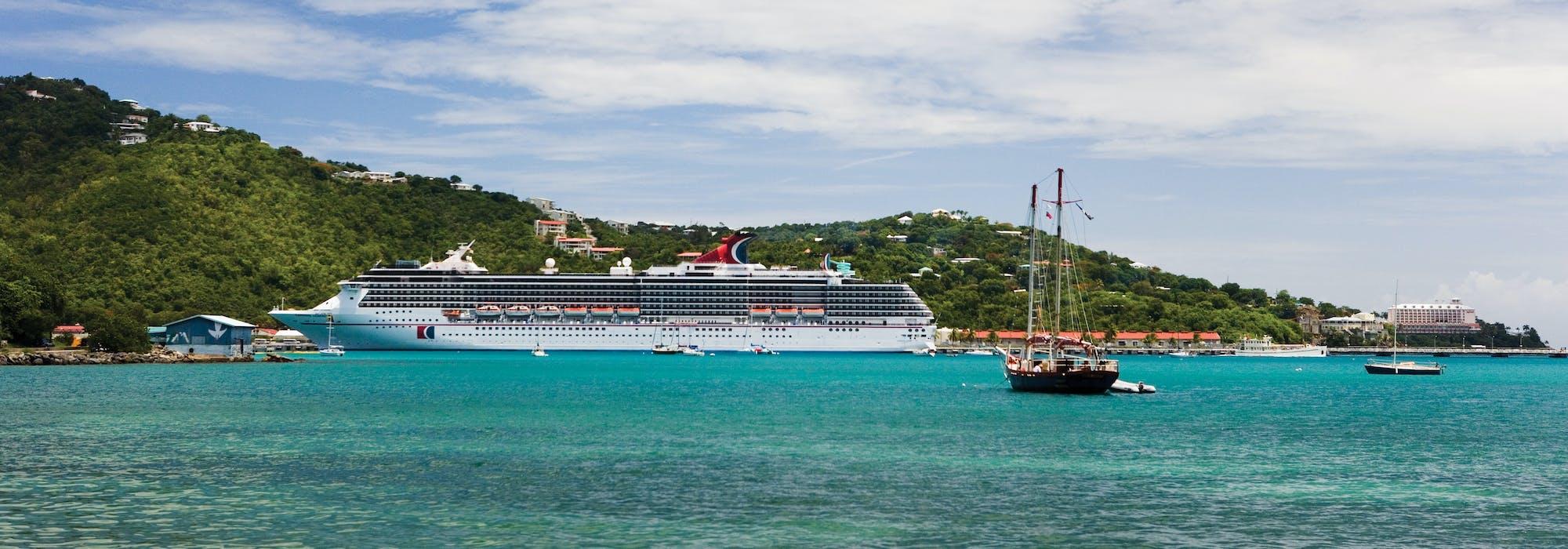 Carnival Legend ligger ankrad i en vacker hamn med klart blått vatten med gröna berg i bakgrunden.