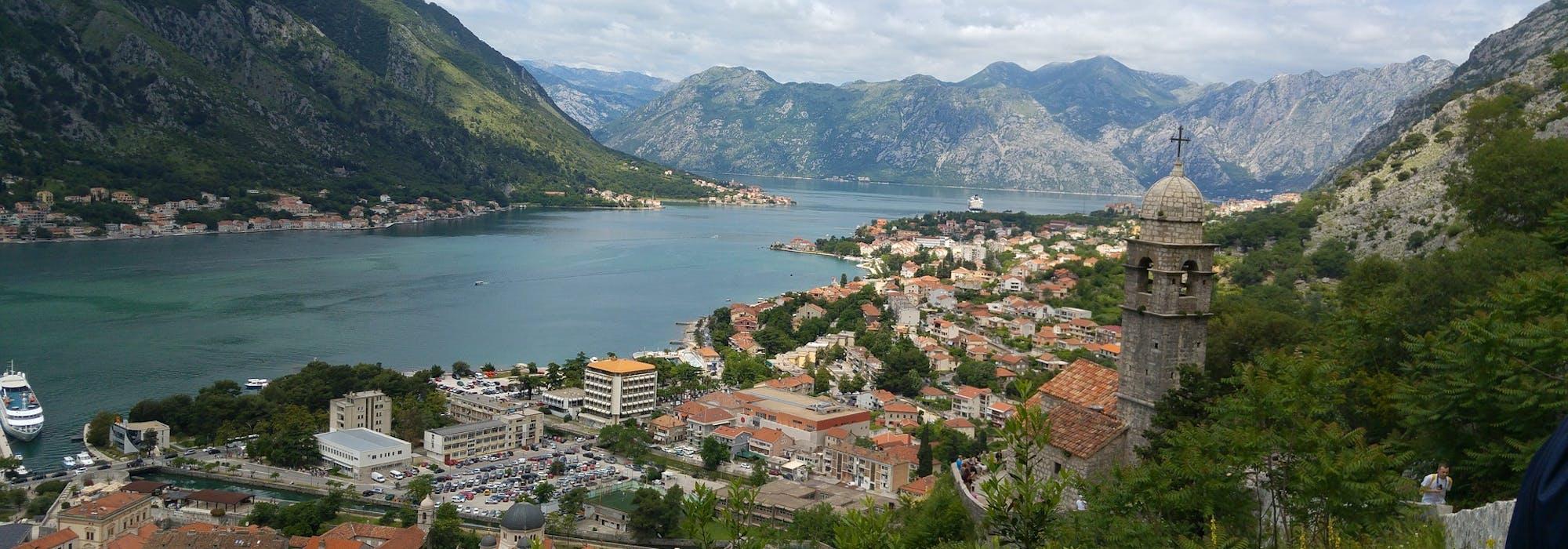 Kotor i Montenegro med berg runtomkring en vik med byggnader och ett kyrktorn på höger sida.