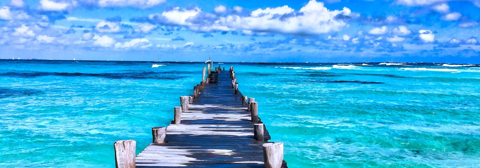En lång brygga sträcker sig ut i det klara, ljusa vattnet.